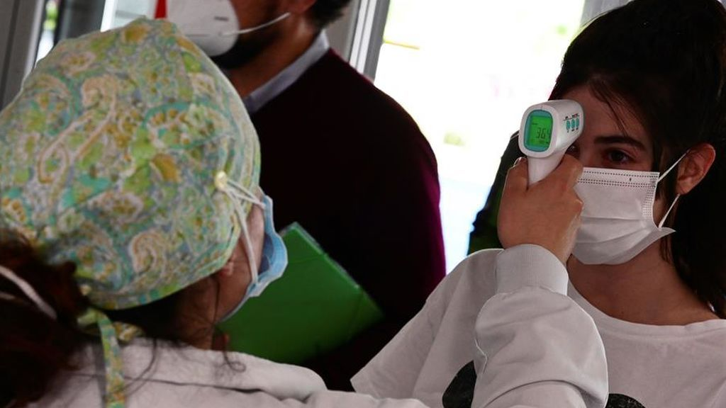 Un sanitario toma la temperatura a una mujer que accede al Hospital de Alcorcón en Madrid