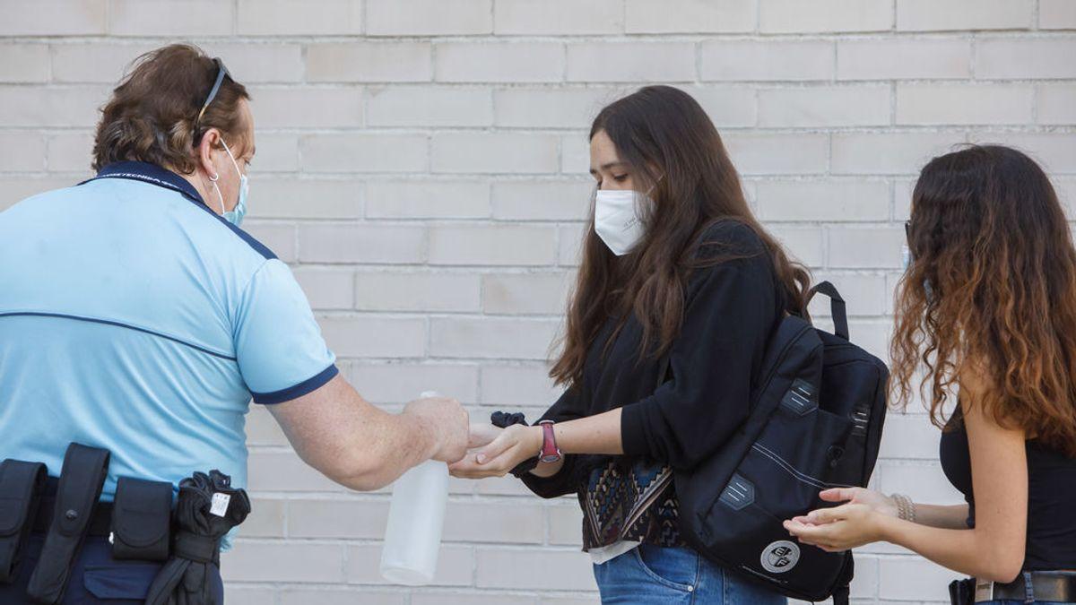 Una estudiante se desinfecta las manos antes de entrar al aula.