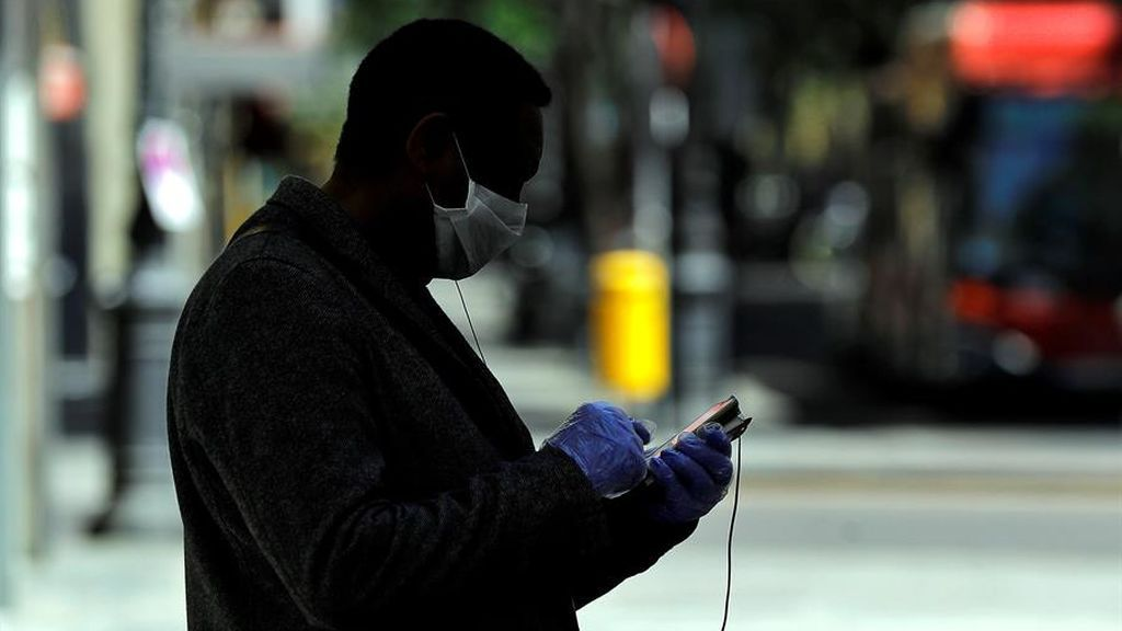 Un hombre su teléfono móvil en una calle de Valencia