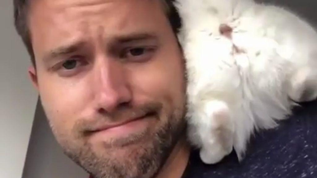 Un chico posando con su gato, aunque el minino esté dando el culo