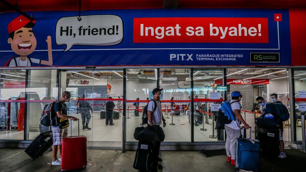 Personas con mascarilla por el coronavirus en una estación de autobuses de Manila