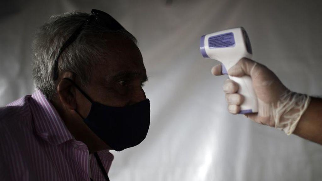 Un hombre registra su temperatura antes de entrar en una iglesia