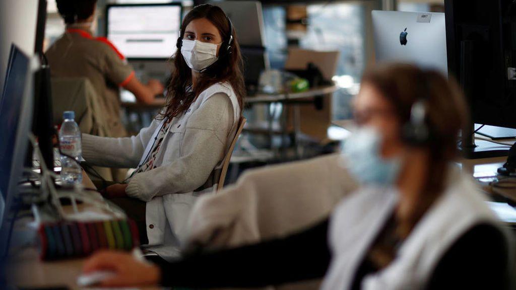 Trabajadores en oficina con mascarilla y medidas de distanciamiento