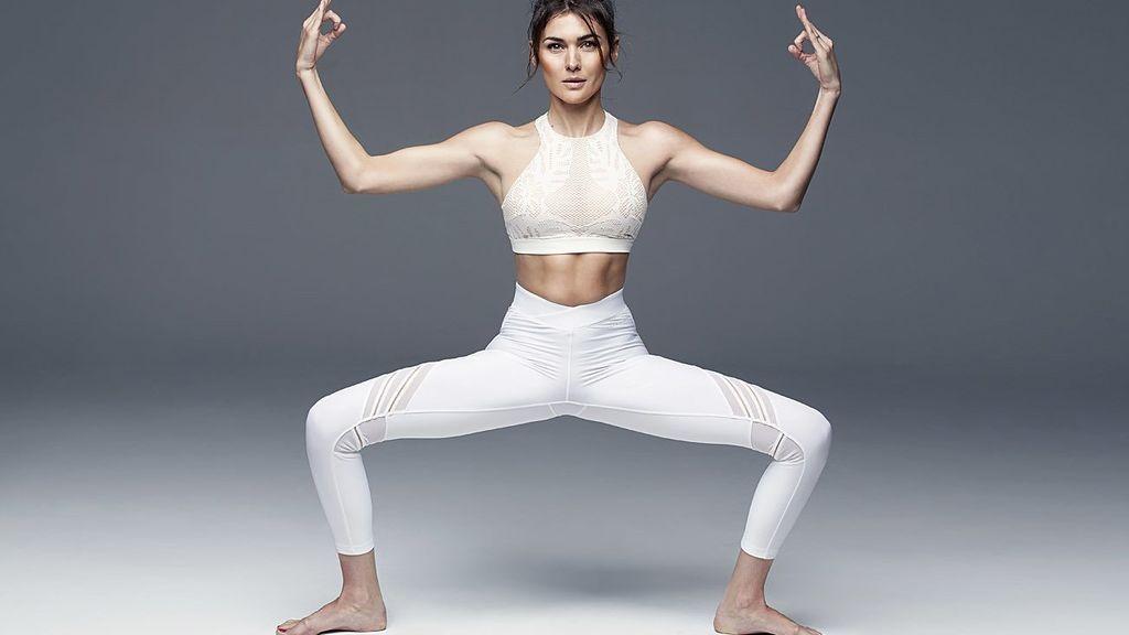 mujer realizando la postura de la diosa mediante una práctica de yoga