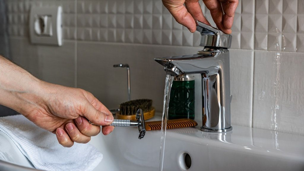 person-holding-stainless-steel-faucet-3944859