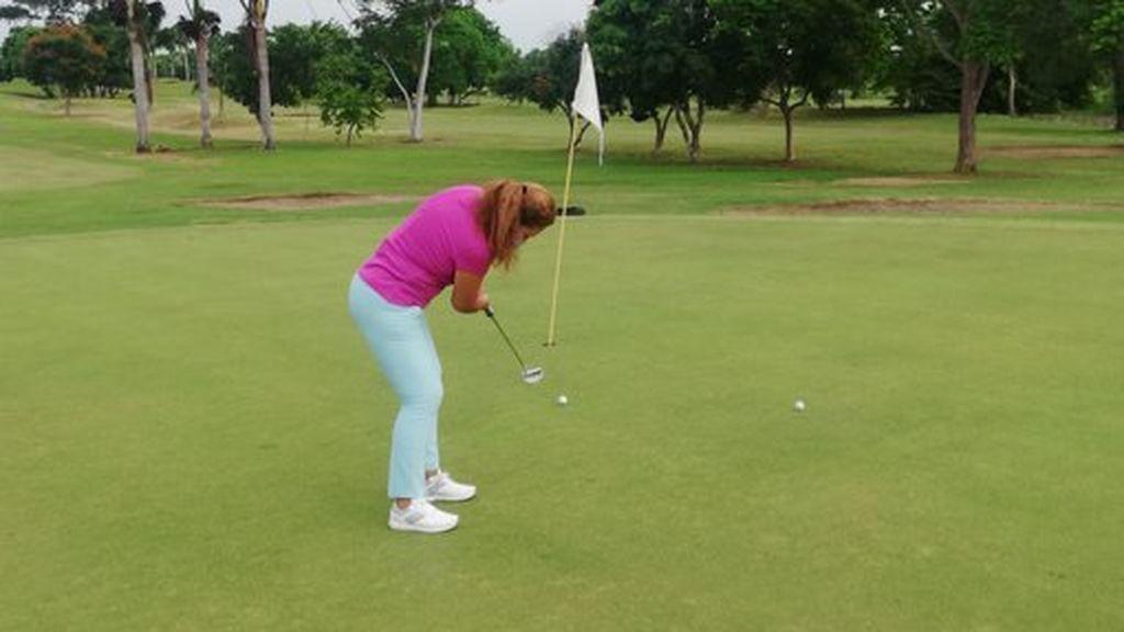 mujer realizando un putter en golf