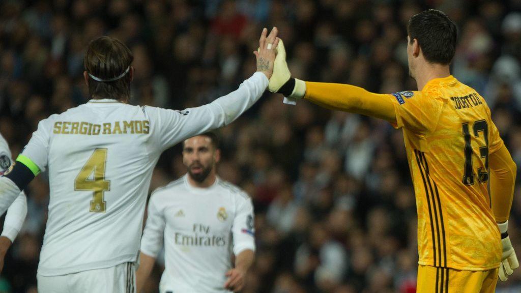 Ramos y Courtois se chocan la mano en un partido.