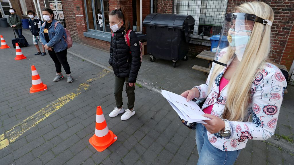 Varios niños esperan entrar a su colegio en Londres