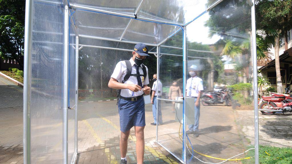 Un estudiante pasa por una cámara de desinfección en Salatiga